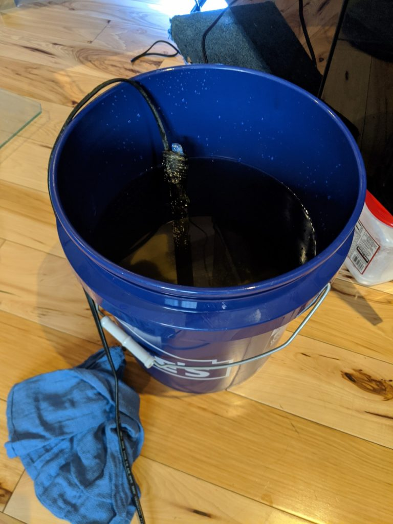Heater in a bucket will warm the water up to a the appropriate temperature for your aquarium